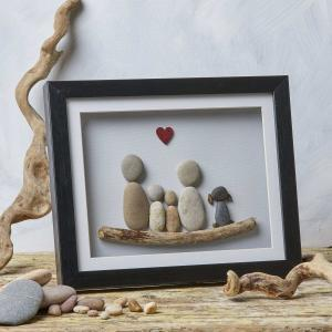 Image of family scene handcrafted with pebble art in frame